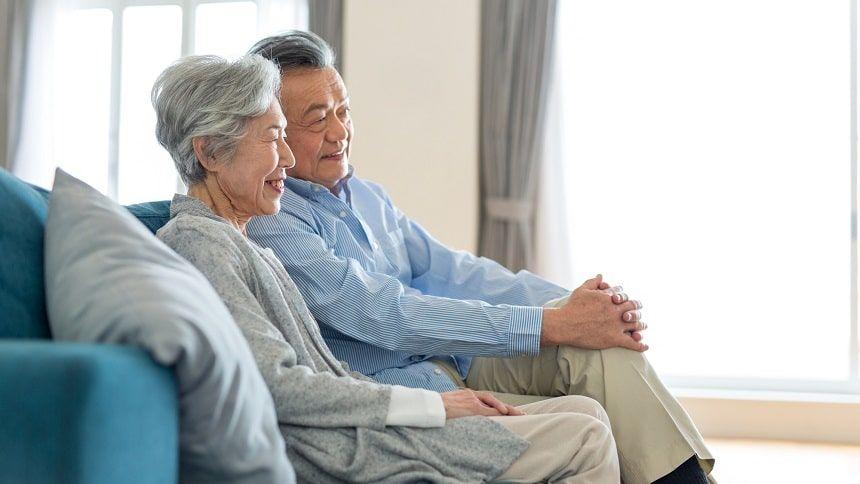 ソファに座り微笑みあう老夫婦