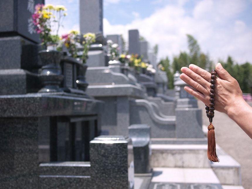 墓前で手を合わせる人