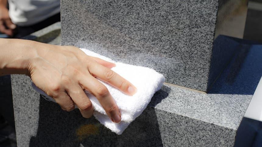 墓石を布で拭く手