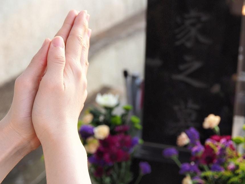 墓石の前で合掌する手