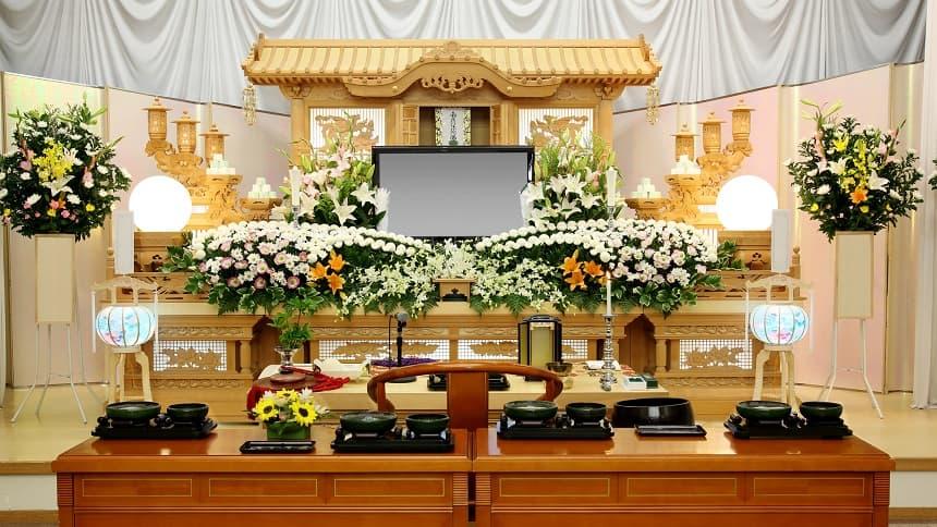 白色の仏花が供えられた暖かな色の祭壇