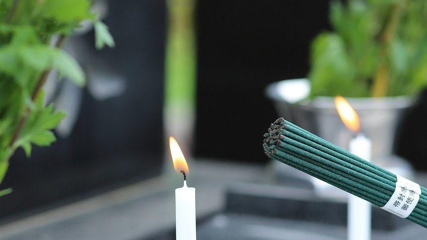 火の灯るろうそくと束ねられている線香