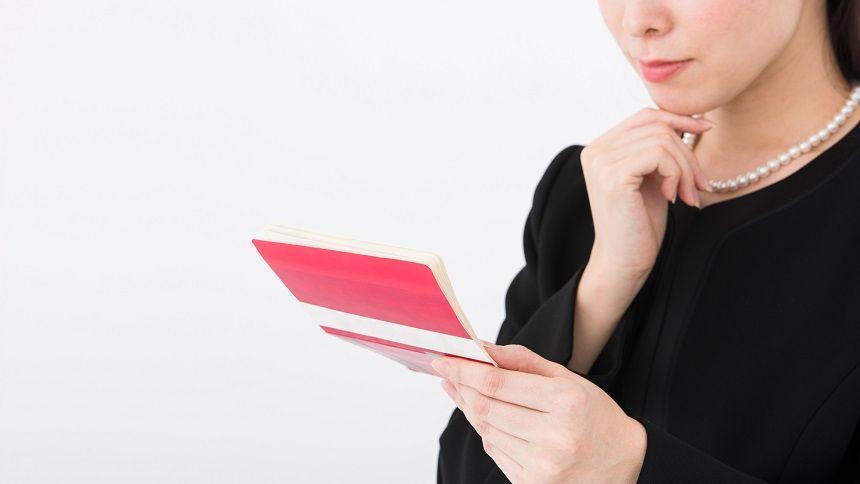 通帳を見て考える女性