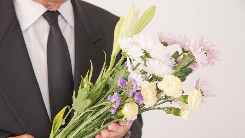 仏花を持つ喪服姿の紳士