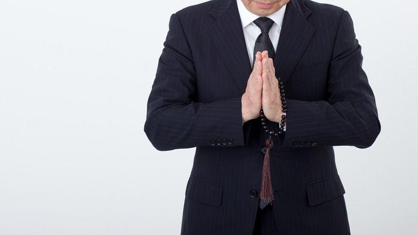 数珠を手に合掌する男性
