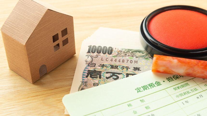 家の模型と通帳と現金と印鑑