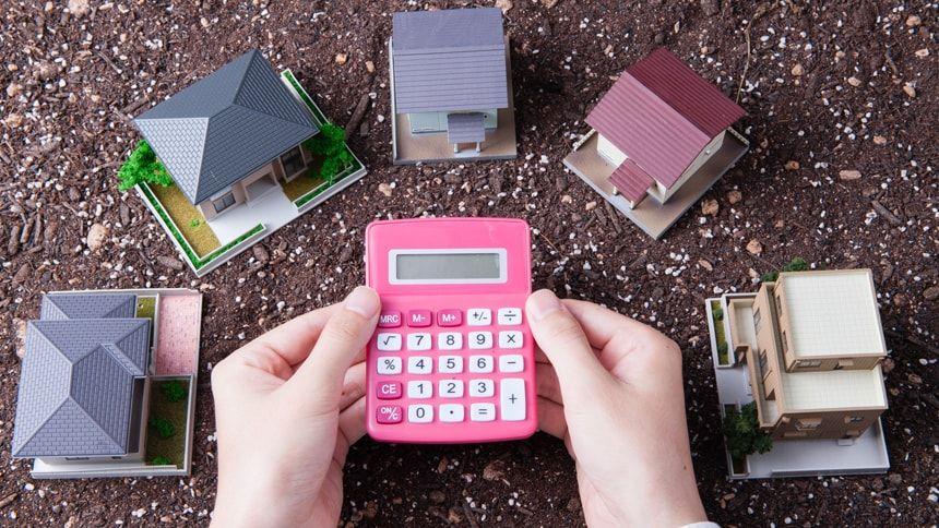 5つの家の模型とピンクの電卓を持つ人