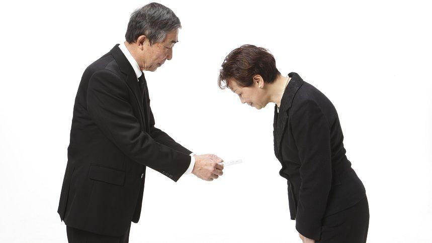 香典を渡す男性と、受け取る女性