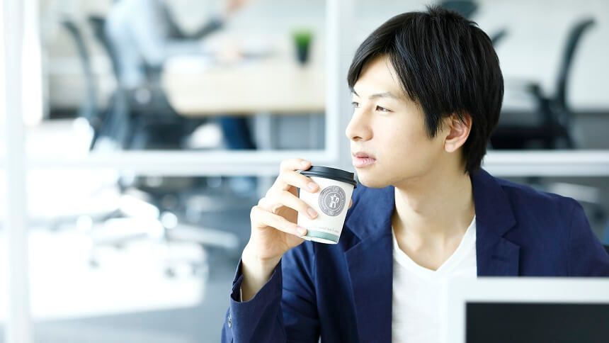 コーヒーを片手に物事にふける男性