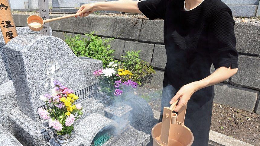 ピアノの形をしたお墓に水をかける女性