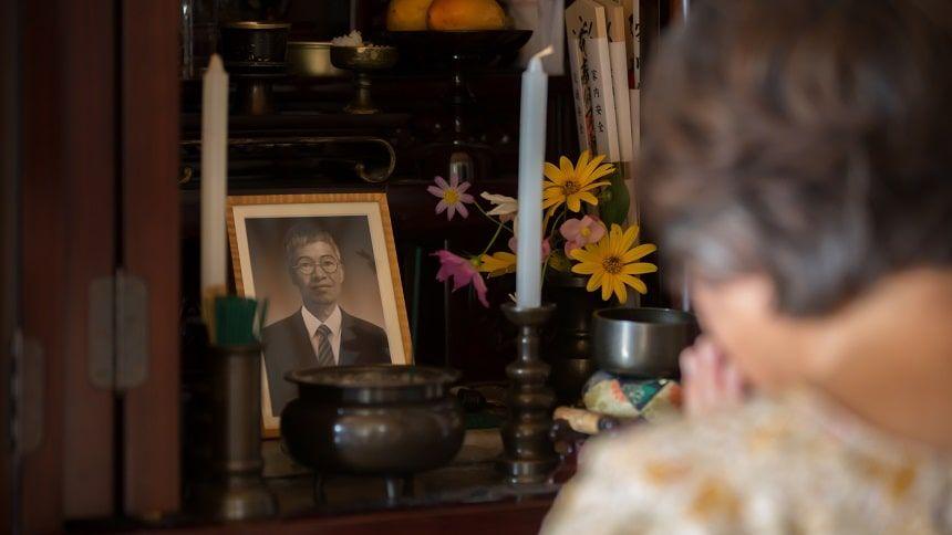 遺影のある仏壇で手を合わせる老婦人